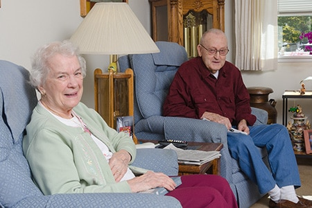 Seniors sitting in chairs at home